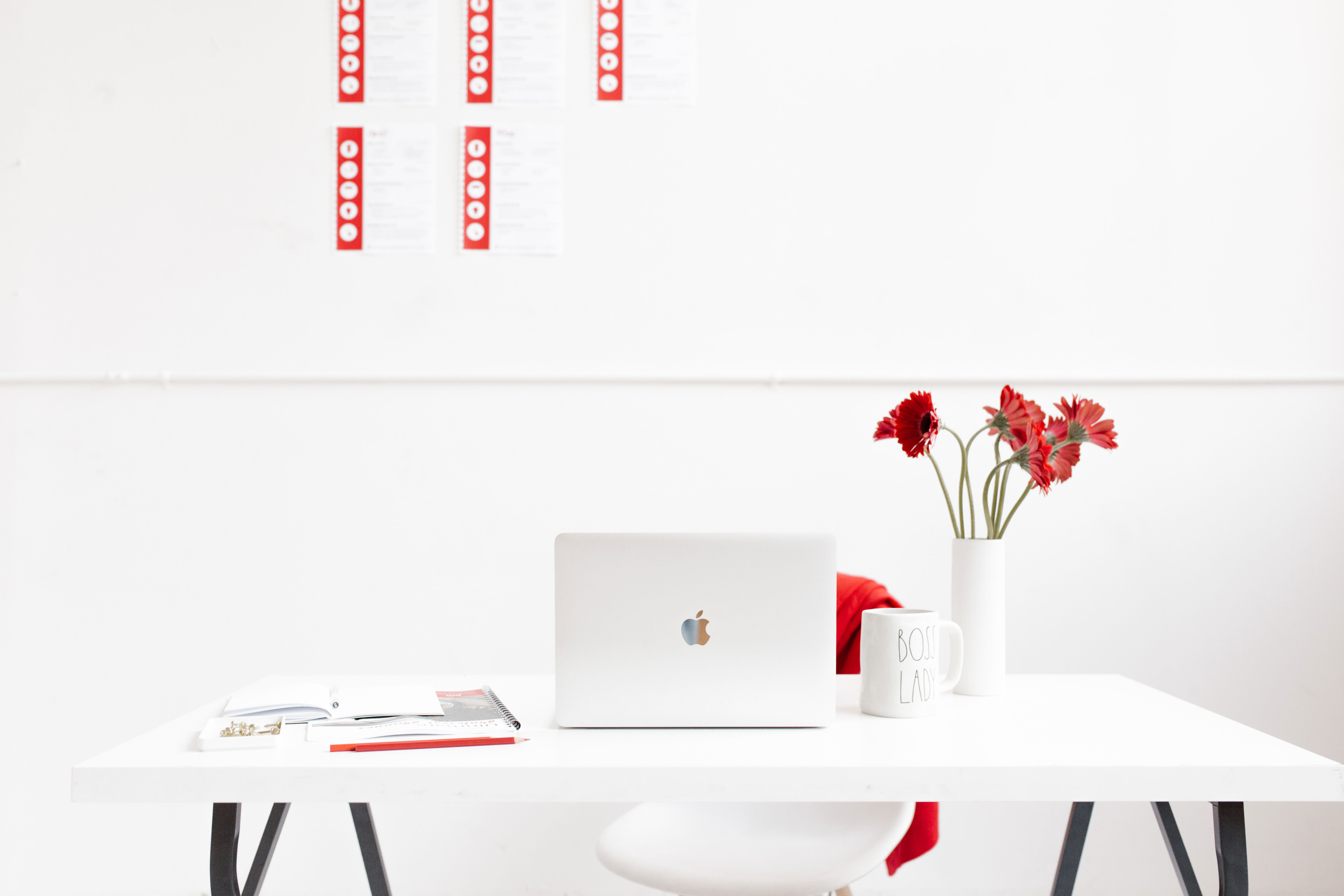 minimalist red and white workspace with planner worksheets taped to wall.