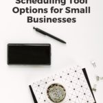 "black & white notepad on desk - text ""Pinterest-approved scheduling tool options for small businesses""."
